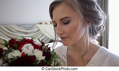 Young bride smell the flowers, and then looking at the camera