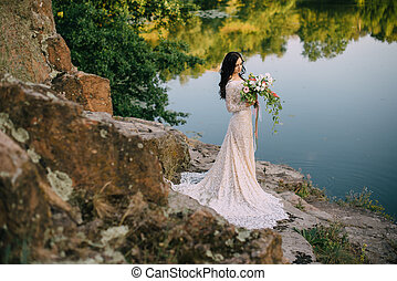 Young bride standing on rocky river bank, sunset