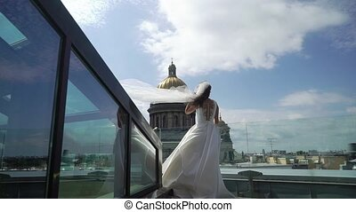 Young bride staying on a terrace roof top with city view...