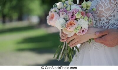 Young bride touching bridal bouquet in a park
