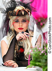 young bride wearing black net gloves and unusual hat sits at table with candle