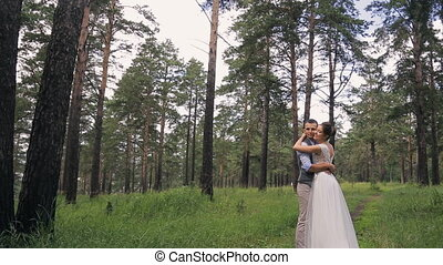 Young bride with bouquet and groom stand in embrace other in forest.