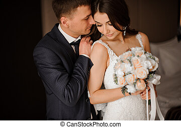 young bridegroom gently hugs his charming bride with a...