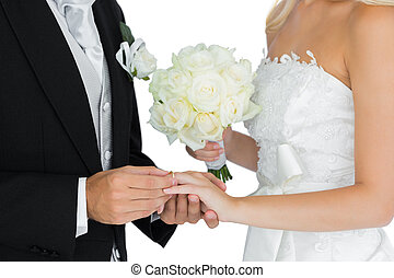 Young bridegroom putting on the wedding ring on his wife's finger on white background