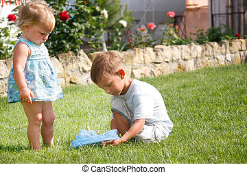 young brother and sister playing in park
