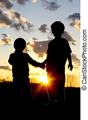 Young Brothers Holding Hands in Front of Sunset