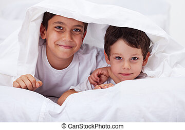 Young brothers together - boys under the blanket