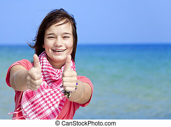 Young brunet girl on the beach show OK symbol.