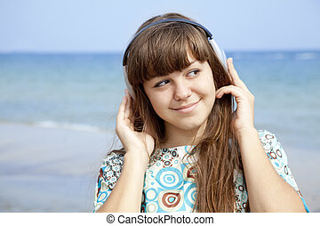 Young brunet girl with headphone on the beach.