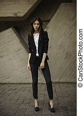 Young brunet woman standing outside in black jacket, jeans