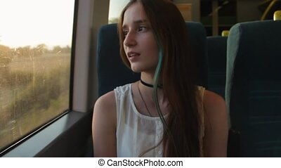 Young brunette beautiful hipster girl with long hair yawns, sitting by the window in the train.