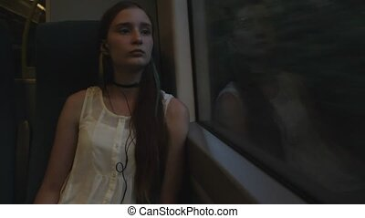 Young brunette beautiful hipster girl with long thinking about her future, sitting by the window in the train.