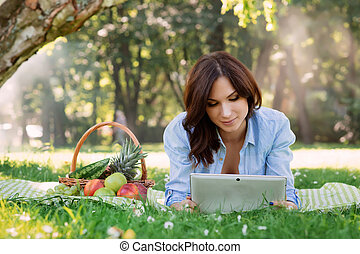 Young brunette being addicted to the tablet on a picnic in the park