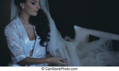 Young brunette bride in elegant white lingerie, peignoir sitting on the bed. Beautiful woman fixs her veil.