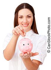 Young brunette businesswoman saving money in a piggybank