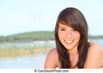Young brunette by lake