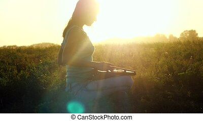 Young brunette caucasian woman typing on a laptop outdoors at beautiful sunset sitting on the grass with amazing lense flare effects. 3840x2160