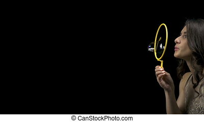 Young brunette girl blowing bubbles on black background