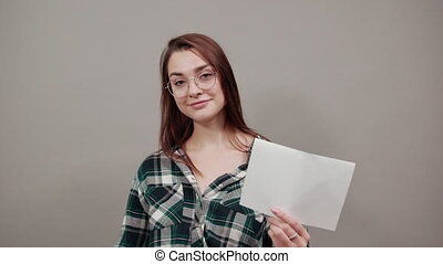 Young brunette girl blue green in checked shirt on grey background happy woman with glasses holds a white sheet of paper in hand, shows her thumb