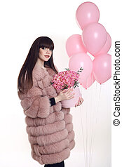Young brunette girl in pink fur coat with rose bouquet of flowers in hat box over balloons  isolated on white studio background.