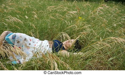 Young brunette girl lies on a green grass, enjoys her life in summer in slo-mo