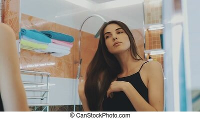 Young brunette girl looking in mirror in bathroom. Touch hair. Check teeth.