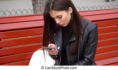 girl uses a cell phone on a bench in the Park