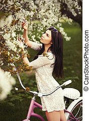 Young brunette girl with a bicycle in a park