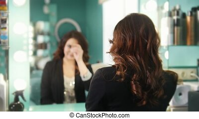 Young brunette in a beauty salon admiring her reflection in...