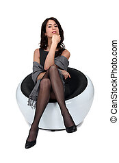 Young brunette in a modern chair.