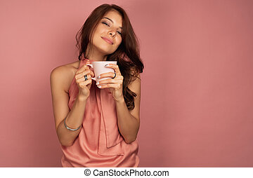 Young brunette in a pink dress enjoys her cup of tea or coffee looking at the camera