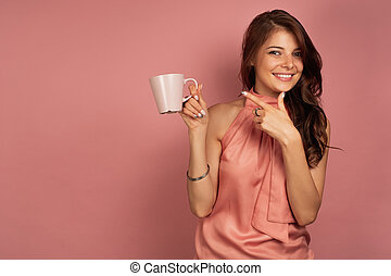 Young brunette in a pink dress points at her pink cup with a smile