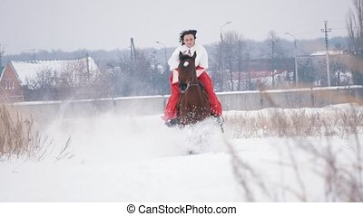 Young brunette in a red dress galloping fast on a horse...