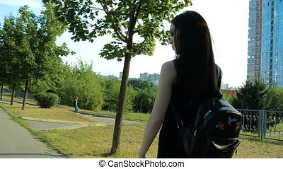 young brunette in black dress and with a backpack walks down the street