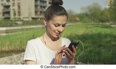 Young brunette in headphones using smartphone