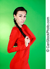 Young brunette in red dress, studio on green background