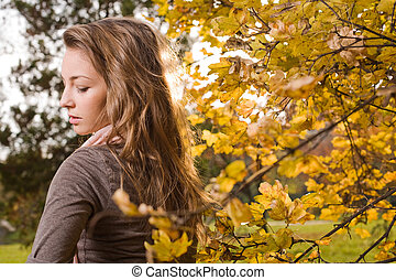 Young brunette in the park at fall
