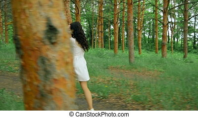 young brunette in white dress walking in the forest