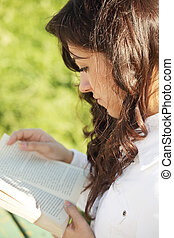 Young brunette in white reading book sideview