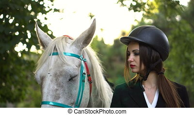 Young brunette jokey girl walking with horse in the park