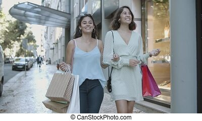 Young brunette ladies looking each other, smiling and chatting. Two best friends walking along street, shopping together and holding bags. Communication, friendship and urban lifestyle concept