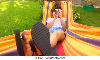 Young brunette laying in striped hammock and using her cell phone, 4K wide shot