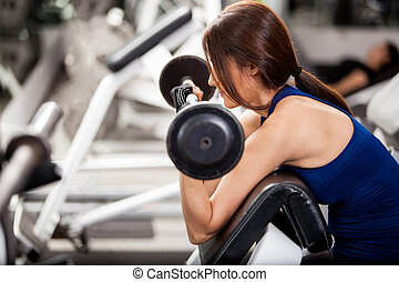 Young brunette lifting a barbell