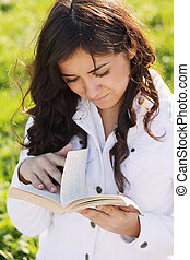 Young brunette looking through book
