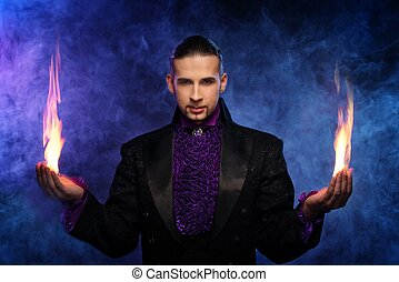 Young brunette magician in stage costume performing flame ...