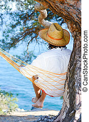 young brunette man in a hat white shirt having fun relaxing relaxing sitting in a hammock on the beach under a tree dreaming & looking into the distance on blue sea copy space background image