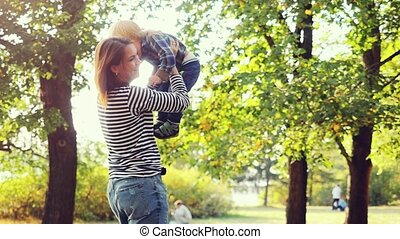 Young brunette mother lifting her son in park having fun enjoying motherhood on sunny autumn day in slowmotion.