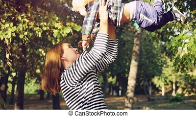 Young brunette mother lifting her son in park having fun enjoying motherhood on sunny autumn day in slowmotion. 1920x1080