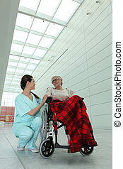 young brunette nurse and elderly dame in wheel chair in hospital