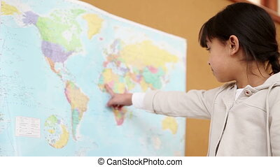 Young brunette pointing a world map